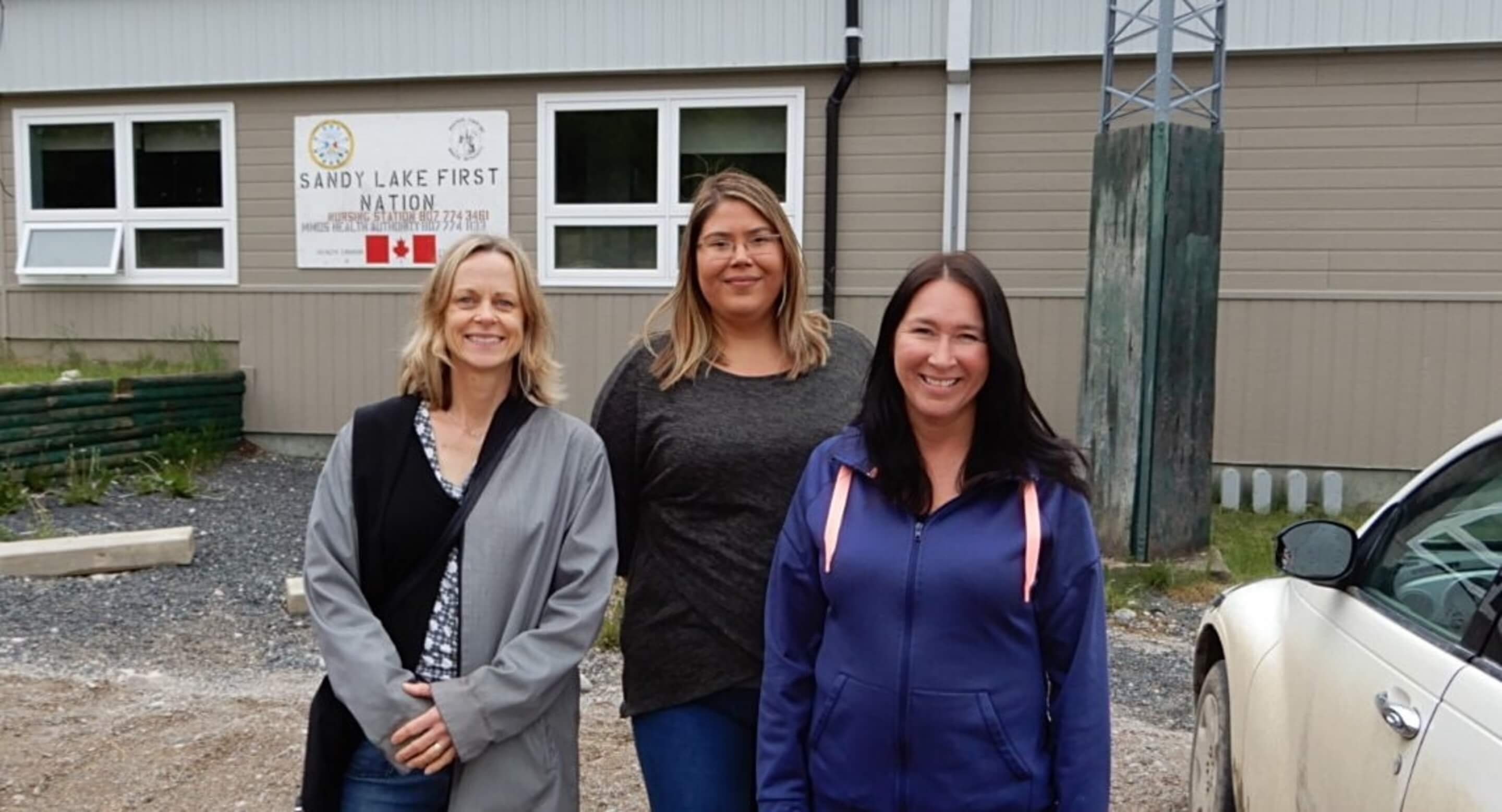 Dr. Samantha Wells, Krystine Abel and Dr. Renee Linklater outside the nursing station in Sandy Lake First Nation