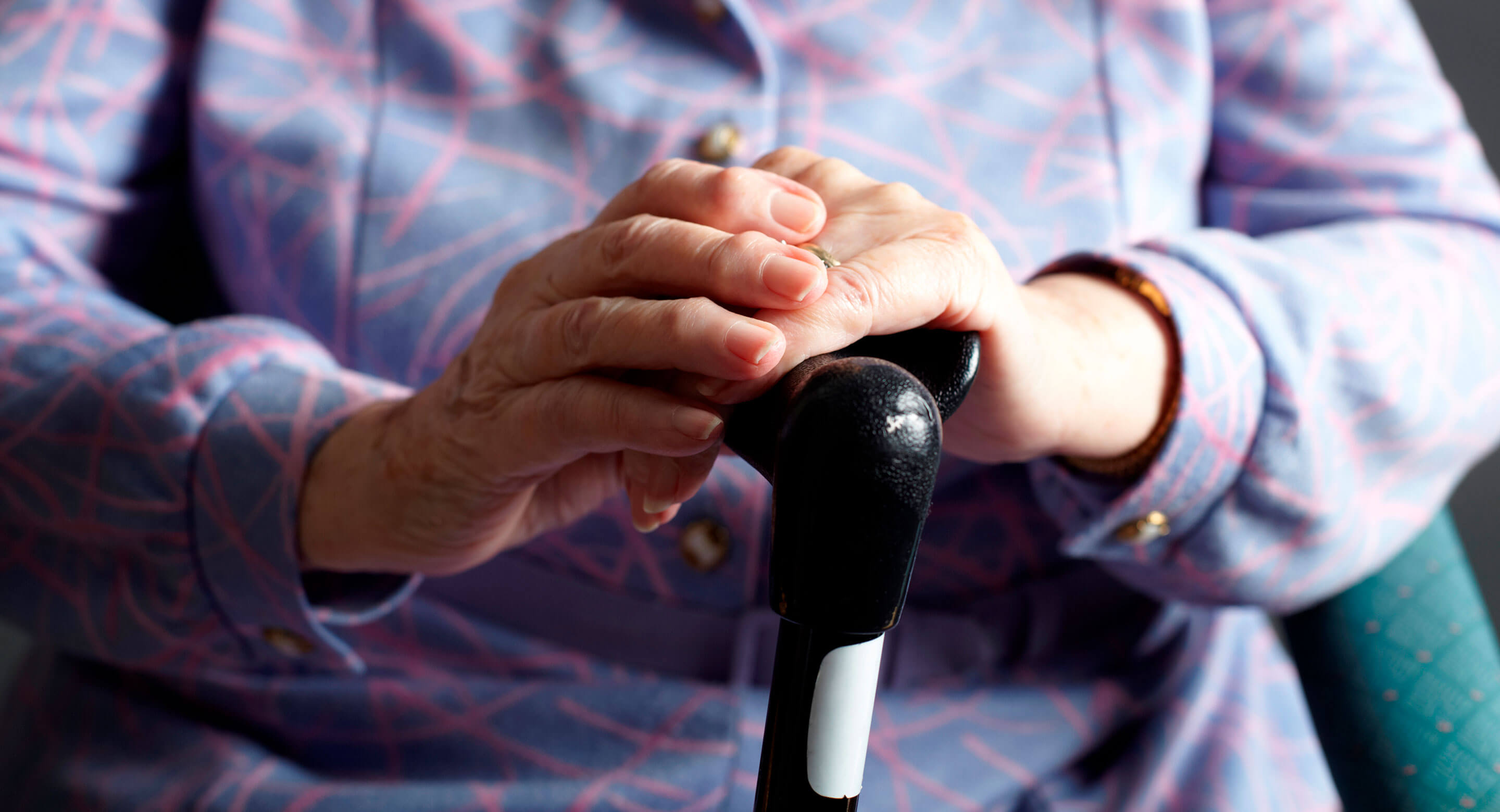 Closeup of hands of elderly woman holding cane.