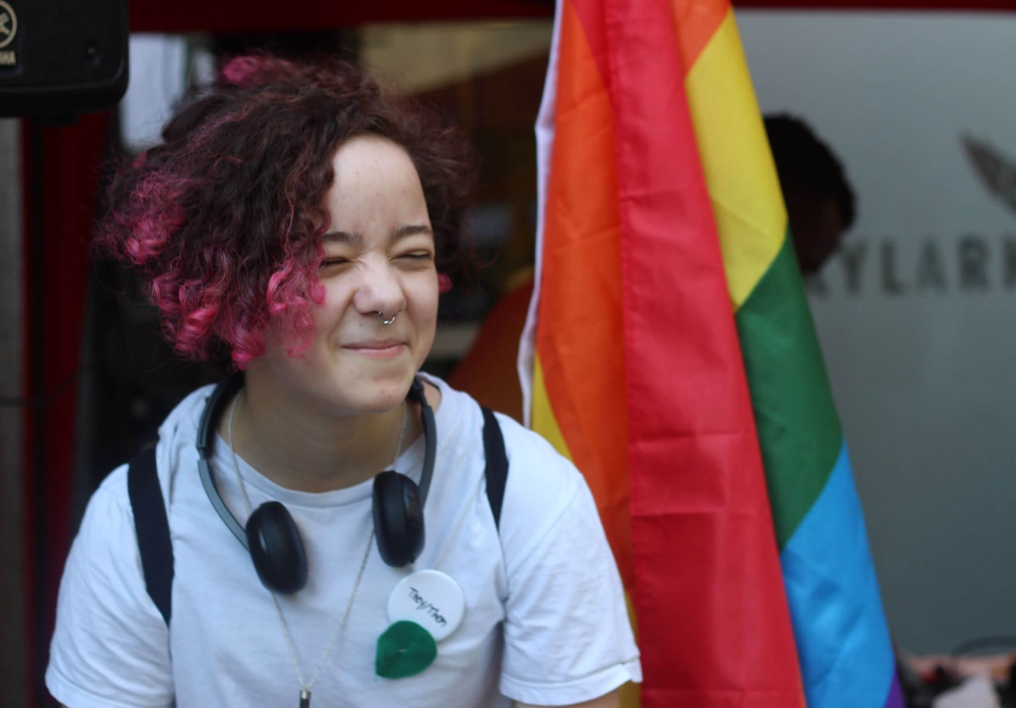 Young person in front of rainbow flag