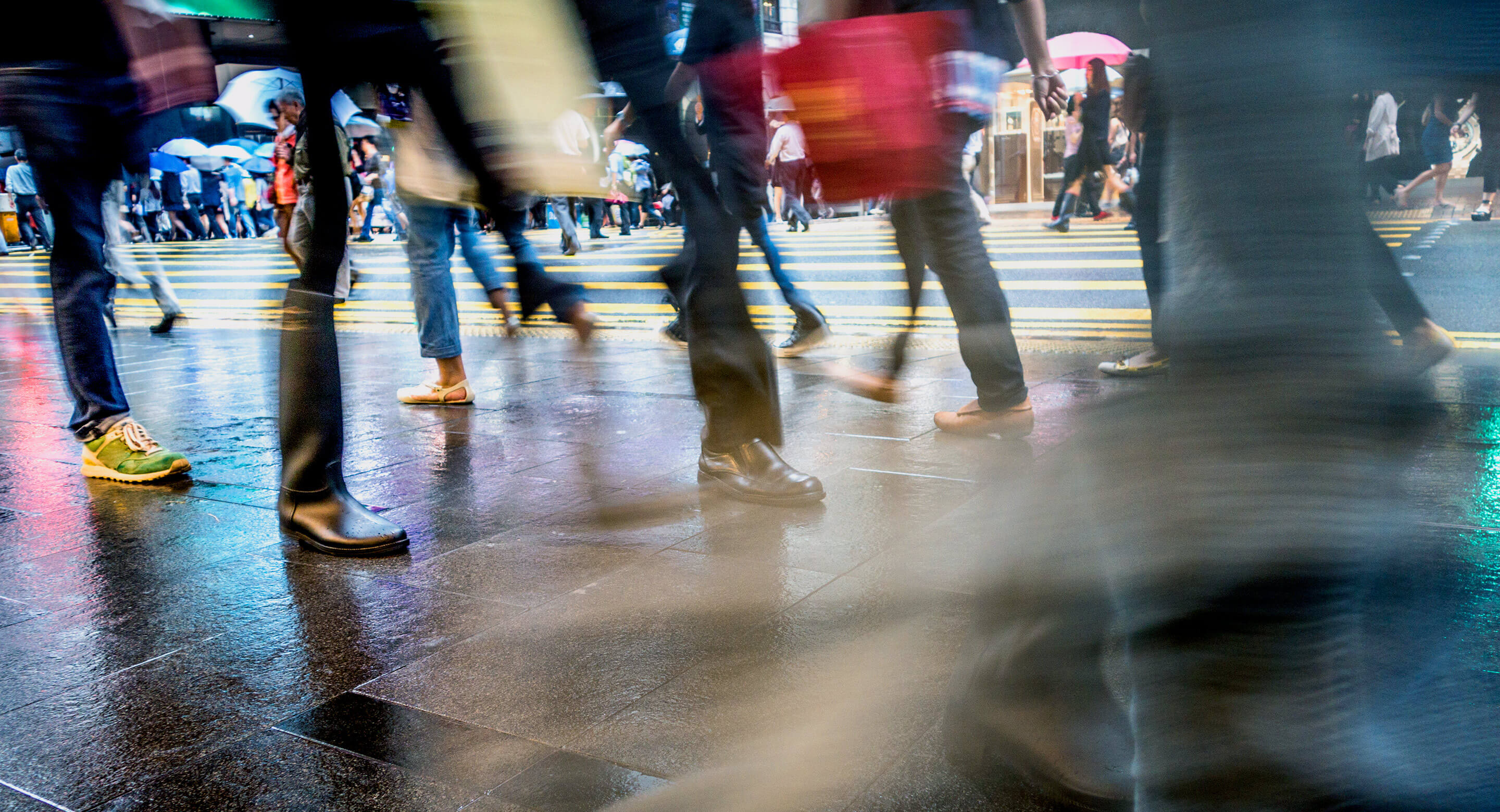 Blurred image focusing on legs and feet of people crossing a street