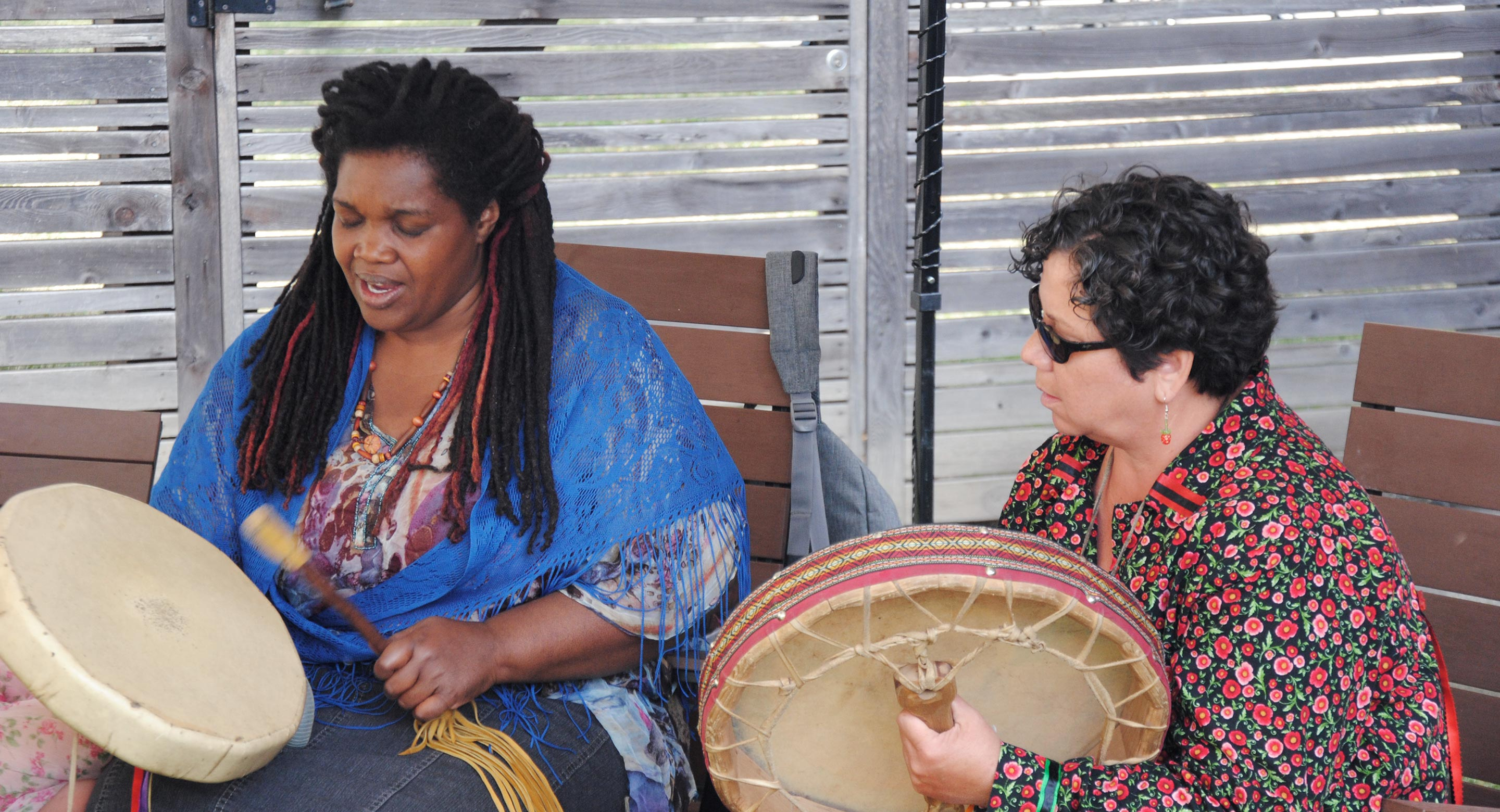 Michele Perpaul and Elder Cynthia White celebrate the opening of CAMH's Ceremony Grounds in 2016 with a drum circle.
